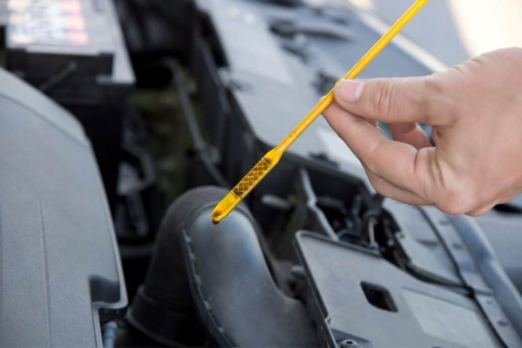 person checking engine oil dipstick