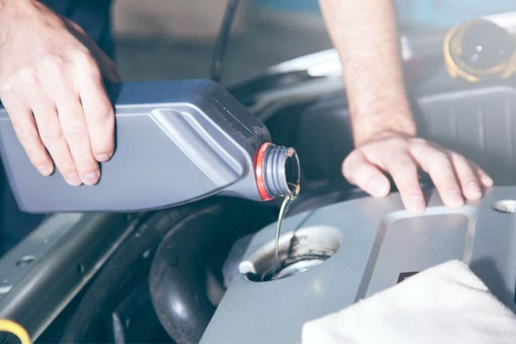 man filling up oil in car