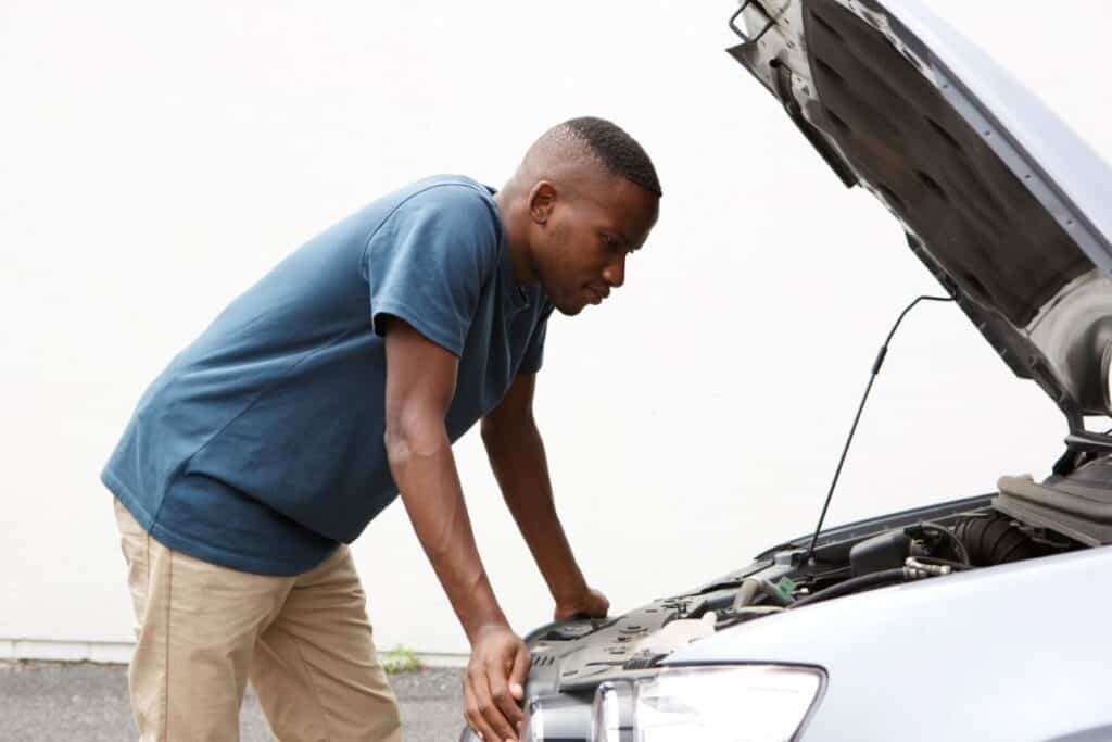 man checking under hood of car